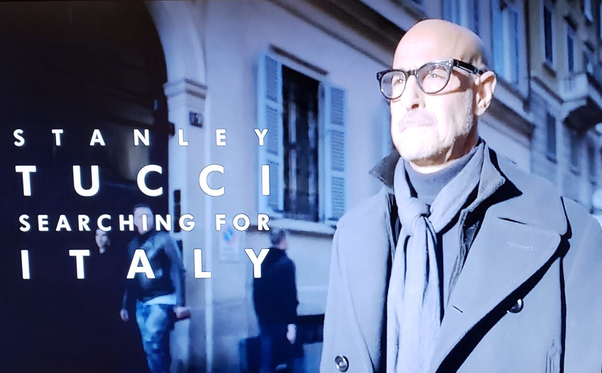 Image from CNN program shows Stanley Tucci in a gray overcoat and European-tied scarf walking down a city street at night in Italy.