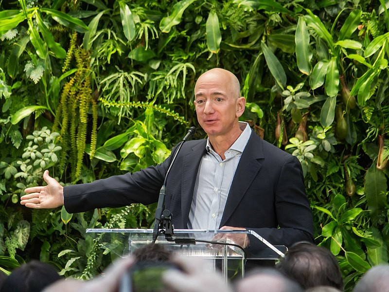 Jeff Bezos giving a speech. A wall of plants behind him.