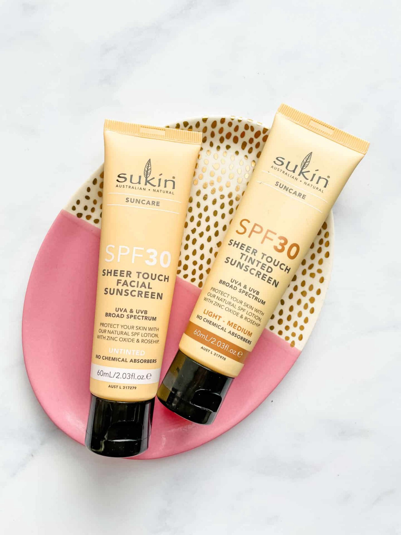 Pale yellow tubes of Sukin Reef Safe Sheer Touch SPF30 Sunscreen in Untinted and Light/Medium on a pink and gold plate