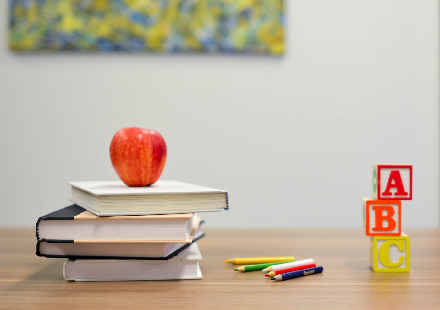 A pile of books with a red apple on top. Next to it is a row of coloured pencils. Next to the pencils is a set of ABC blocks.