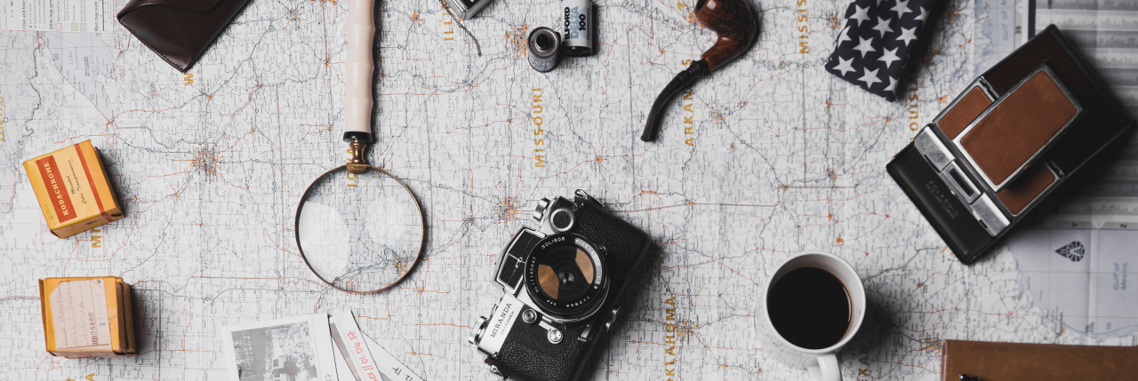 A detective's magnifying glass, a pipe, an an old camera and rolls of film rest on a map, along with a half-drunk coffee