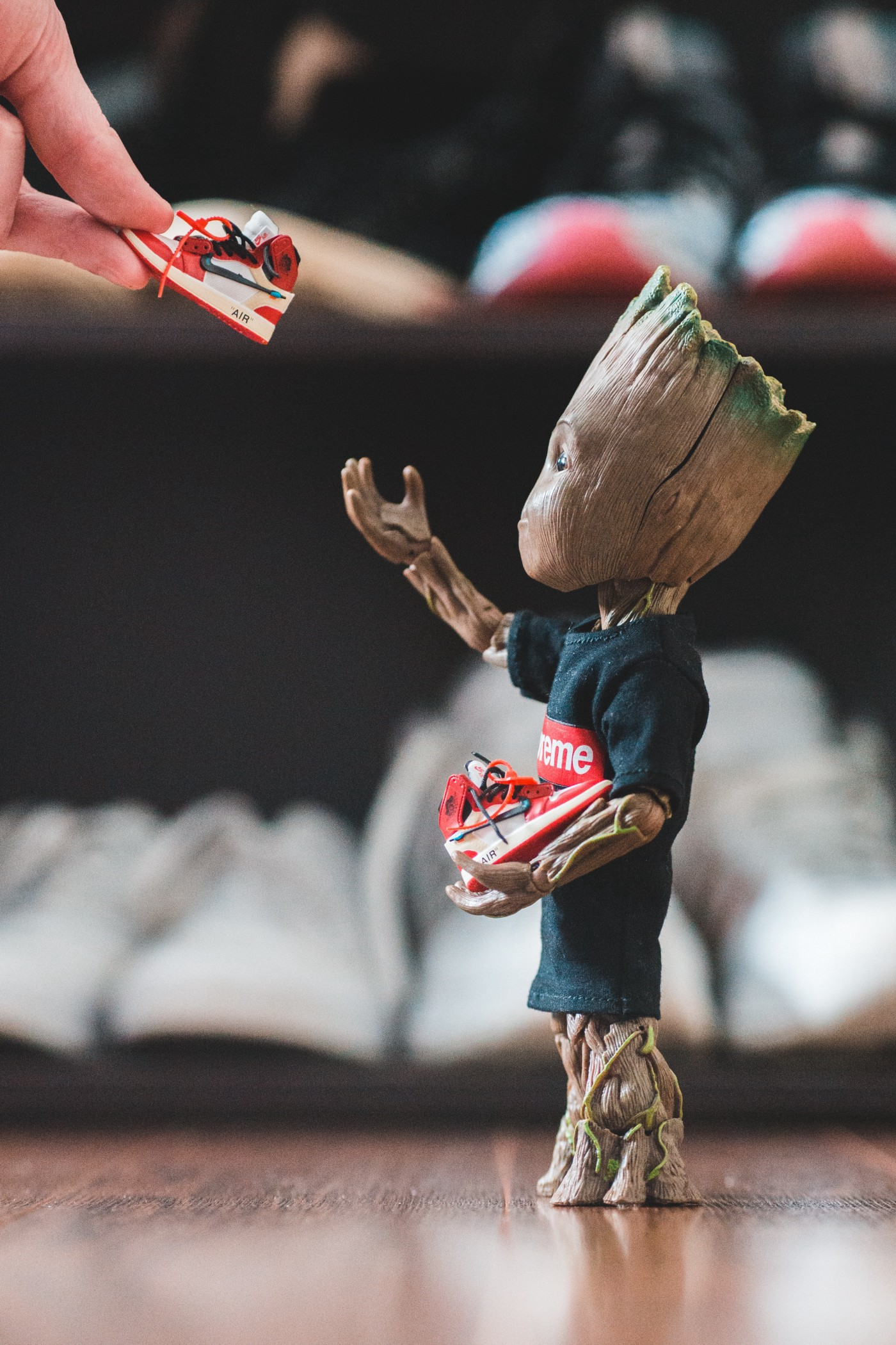 Model of baby Groot accepting a pair of shoes from a hand (of a Man)
