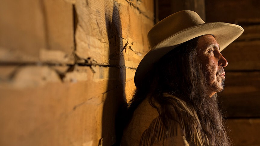 Long-haired man in cowboy hat leaning against log cabin wall