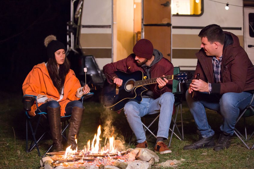 Three people sitting around a campfire in front of an open RV decorated with outdoor lights. One is roasting a marshmallow, one is playing the guitar, and the other is holding a beer.