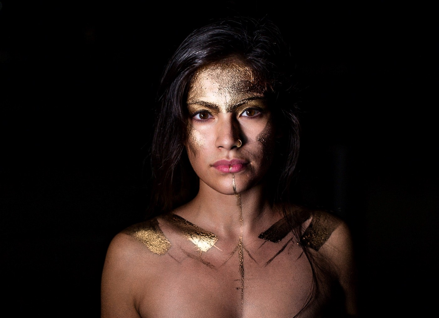 The head and shoulders of a young woman wearing nothing but gold face and body paint.