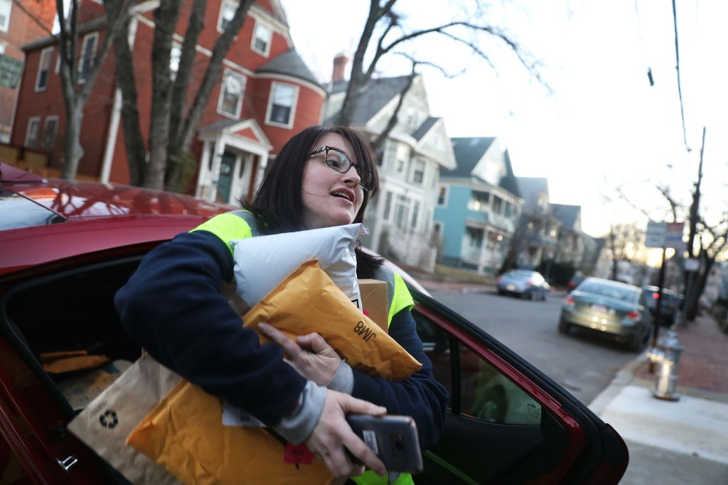 A photo of a gig worker delivering Amazon packages. She has a bunch of packages in her hands and is getting out of the car.