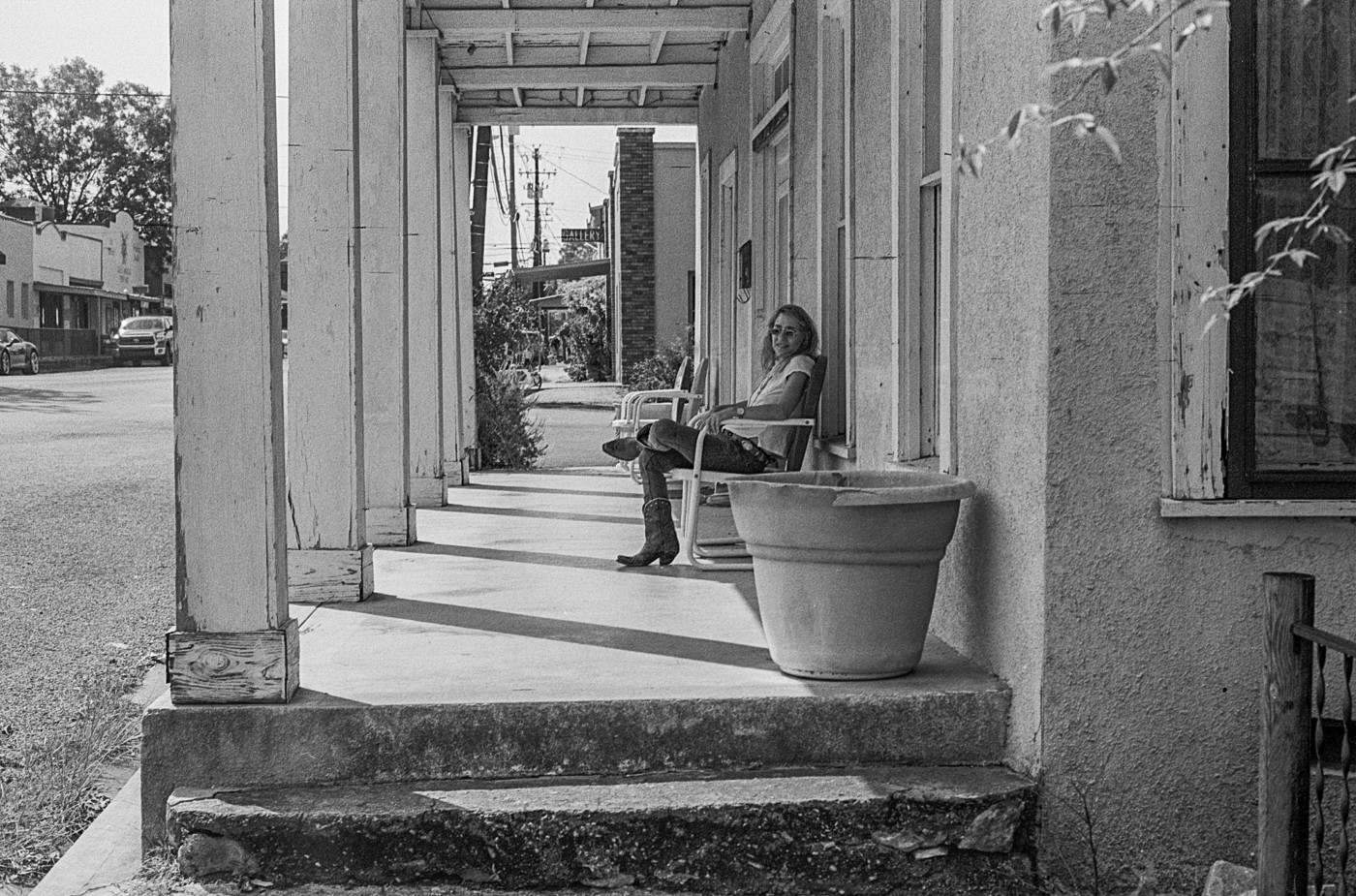 Black and white photo of a woman in a chair on a porch, with cowboy boots and sunglasses on