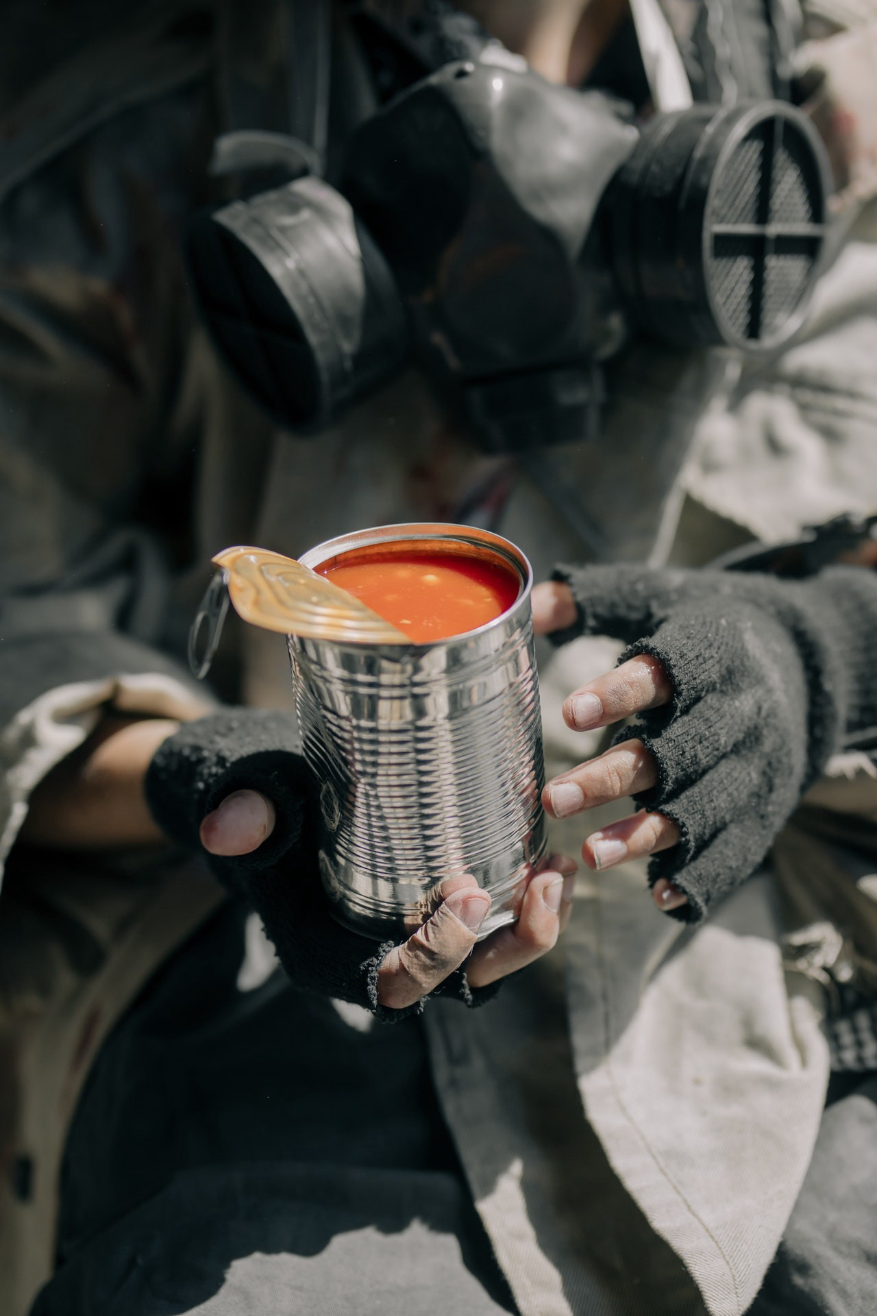 Closeup of a man's hands in fingerless gloves. He's holding a tin can of tomato soup.