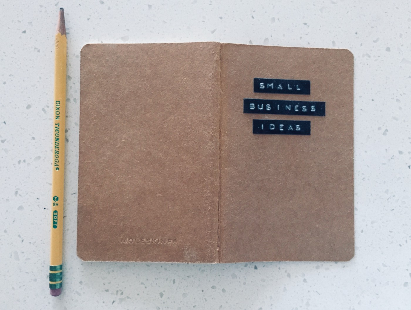 """Pencil and notebook reading """"Small Business Ideas"""""""