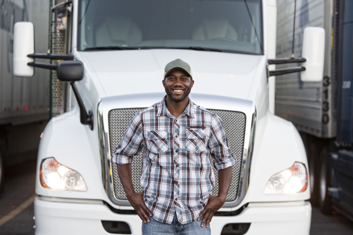 Military Driver Program enabling Veterans; a driver in front of a truck.
