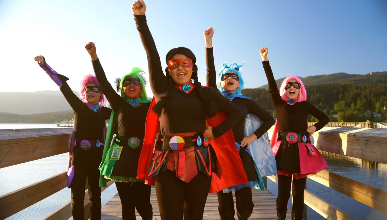 """Five young """"Apprentice Planet Protectors"""" strike a pose in their colourful superhero costumes on a wooden pier."""
