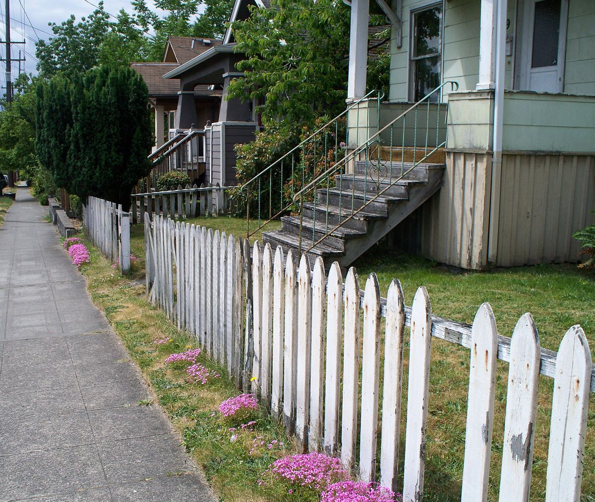 A decaying white garden fence, in front of a worn out blue house.