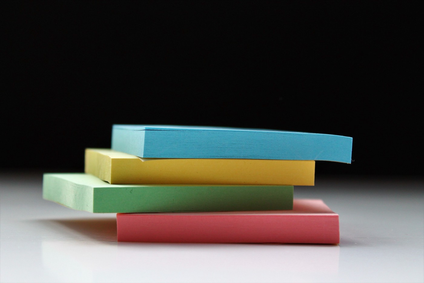 A stack of three pads of Post-it notes on a dark background.
