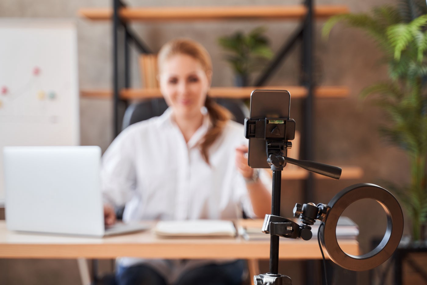 Woman at a desk in front of a ring light and phone on a tripod.