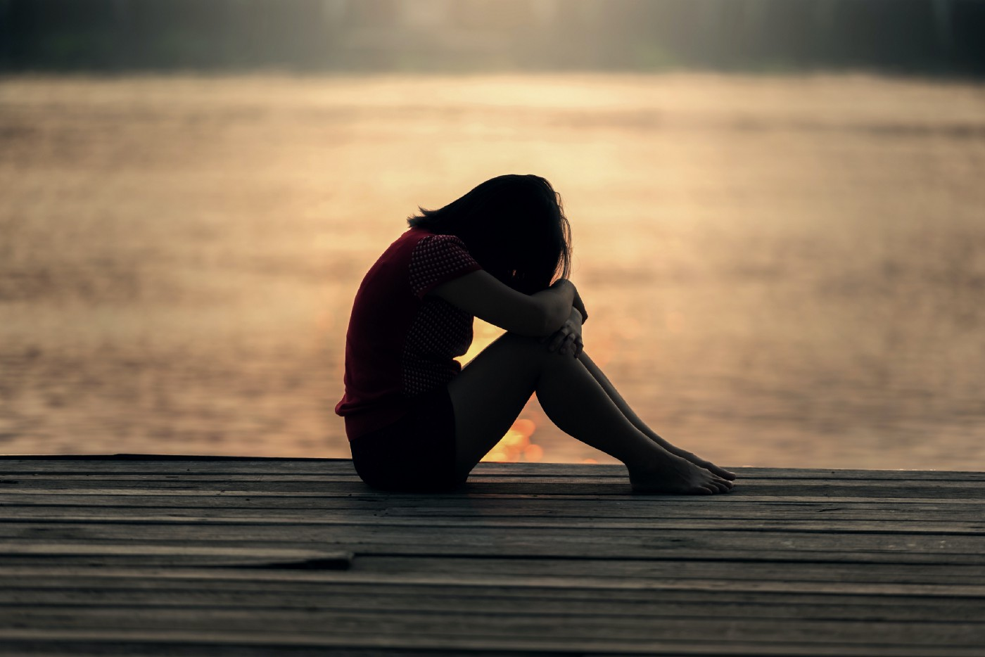 A sad girl sitting on a wooden ledge with her head bowed to her knees and the water shimmering in the background with mellow evening light.