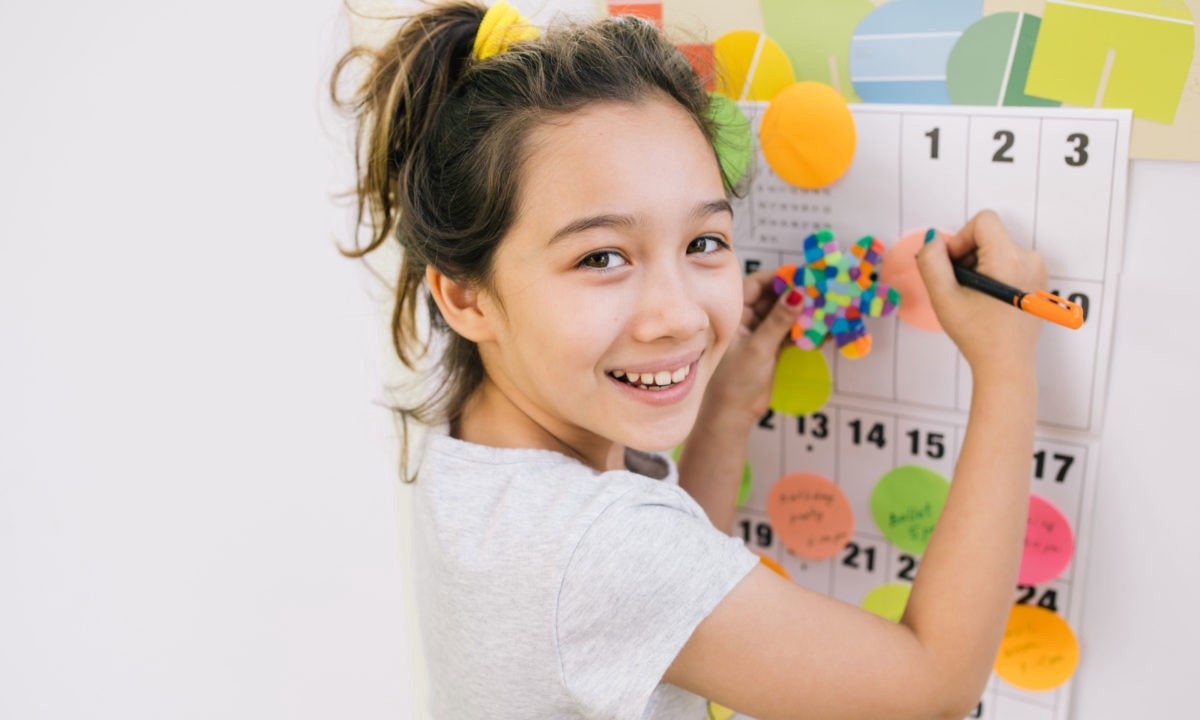Smiling girl using a sticker chart