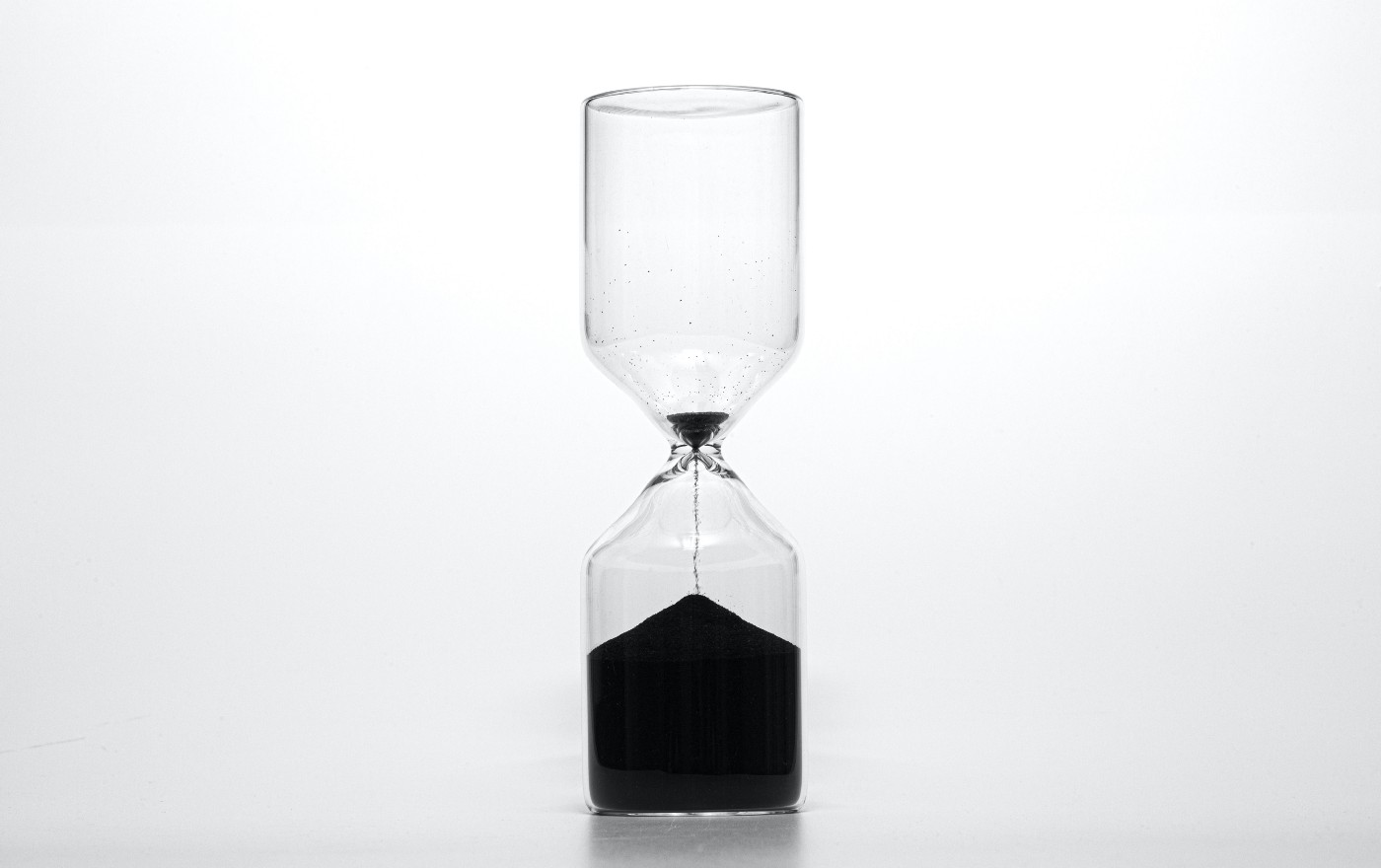A hourglass is shown with most of the sand on the bottom. Only a little bit of sand is at the top with it flowing into the bottom.