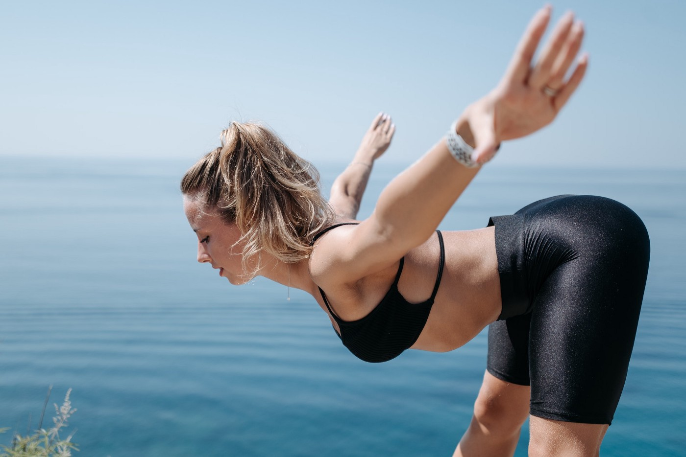 Woman in yoga pose at the beach.