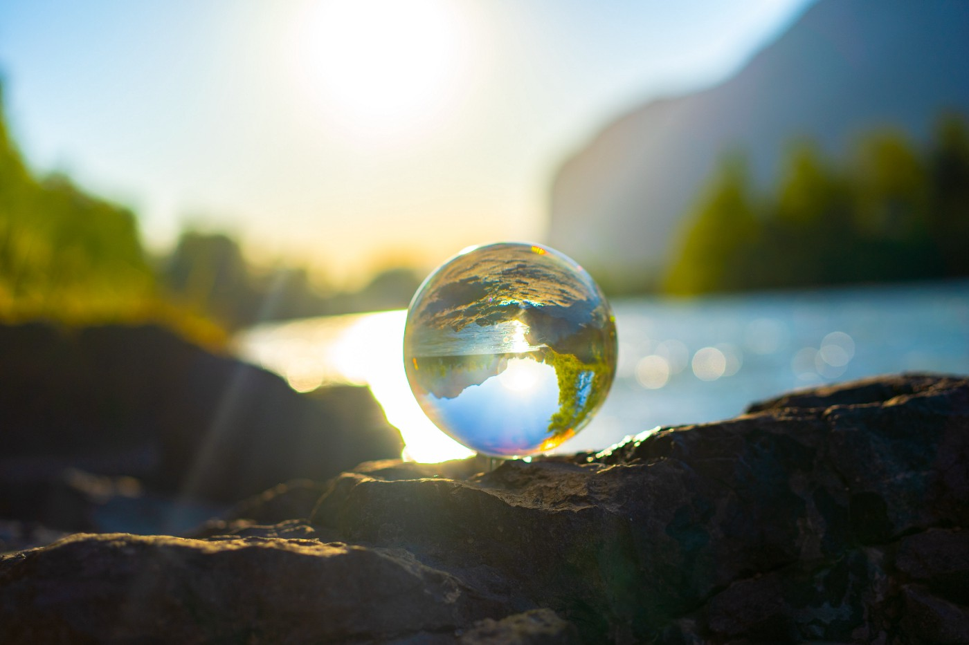 A glass ball reflects the scenery behind it, a mountain, lake, and trees, to create a mirror image of the earth.