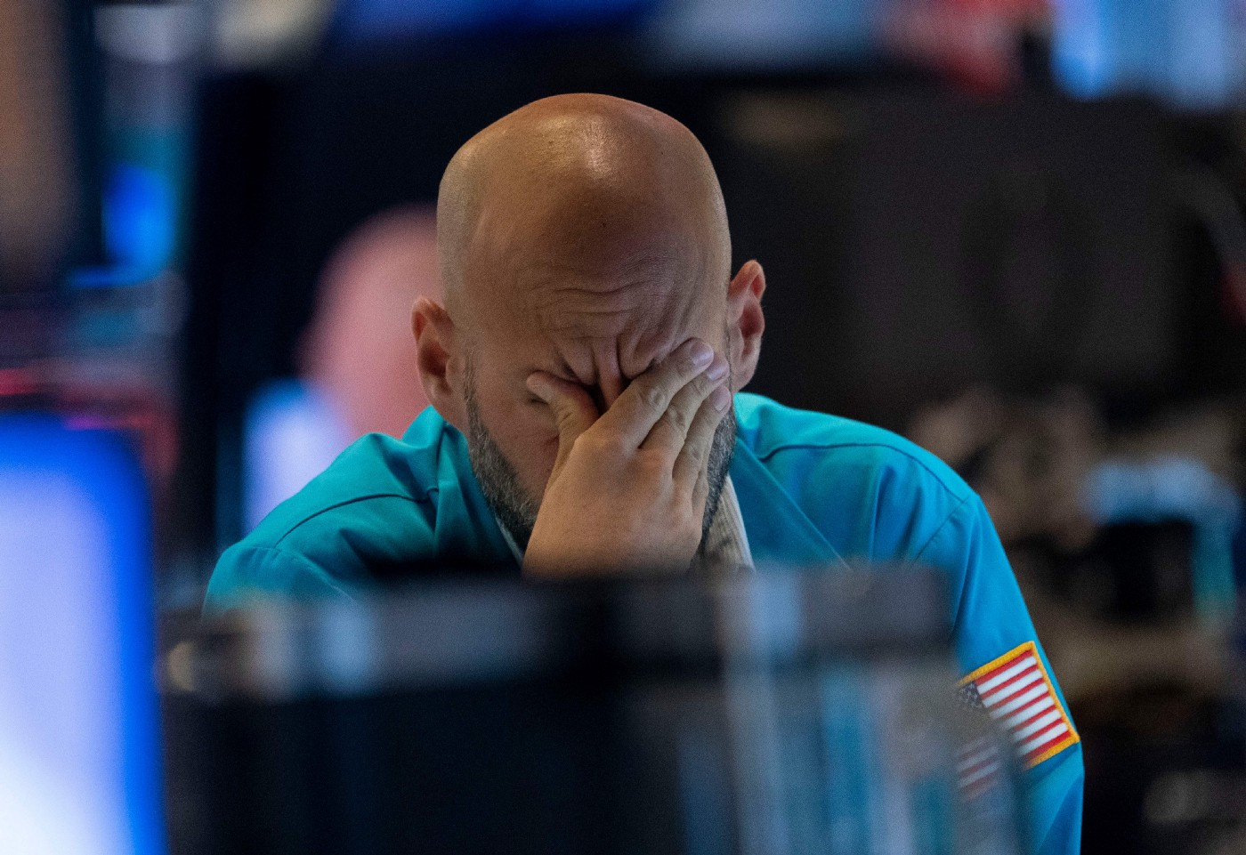 A photo of a trader wiping his eyes as he watches stock prices at the New York Stock Exchange.