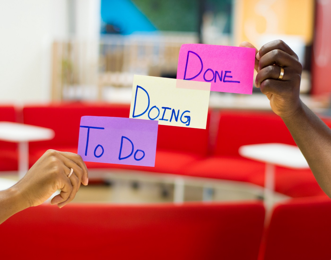 A picture of hands holding sticky notes with the words 'To Do', 'Doing', and 'Done' written on it.