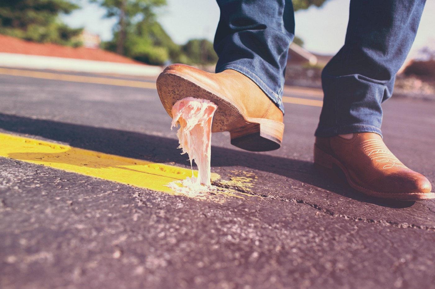 A person wearing blue jeans stepping on pink gum on the road