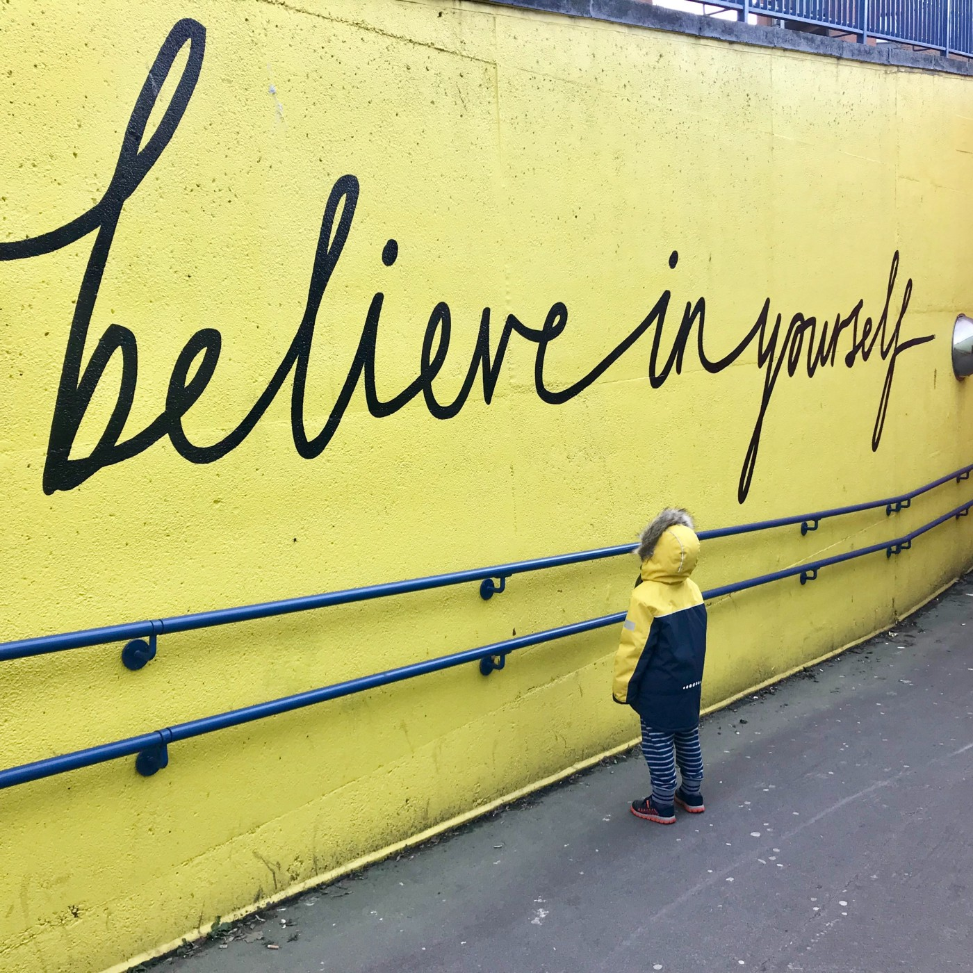 """A young boy looking at a wall painting where the words """"believe in yourself"""" are painted"""