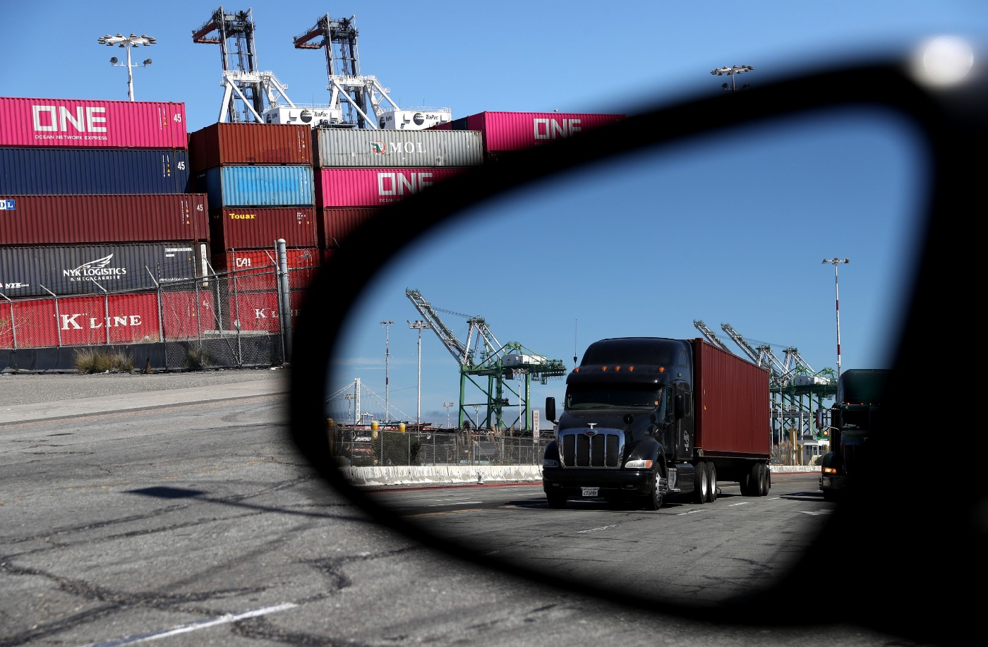 A truck loaded with a shipping container drives through the Port of Oakland on September 03, 2019 in Oakland, California.