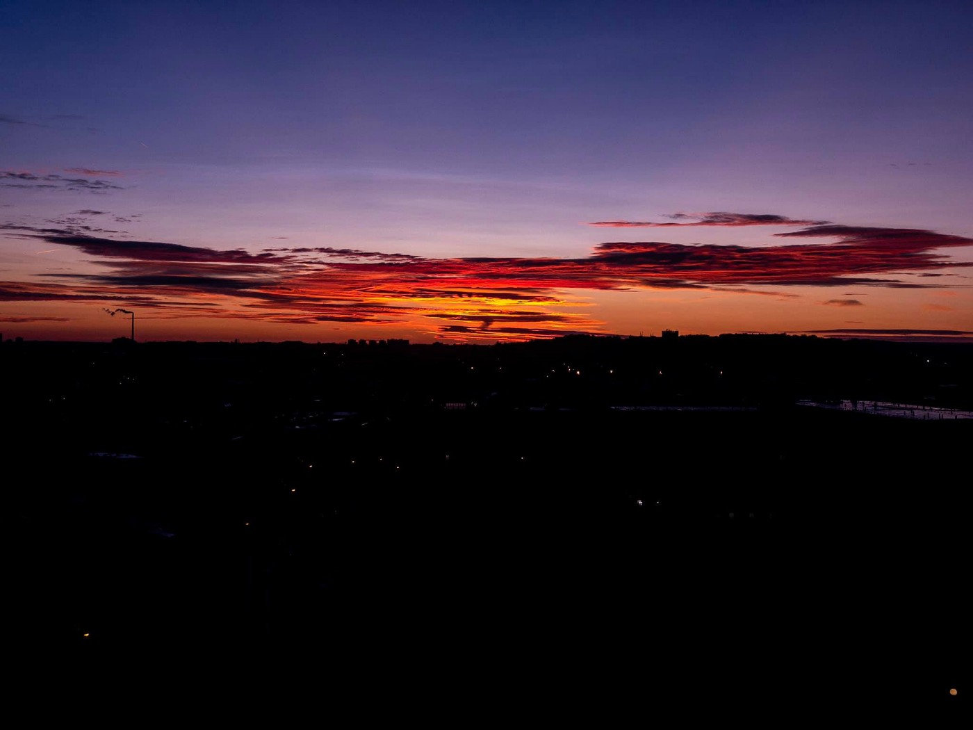 Sunrise over Prague, Czech Republic. Dark landscape with the first hints of orange and red layering up to streaks of cloud.