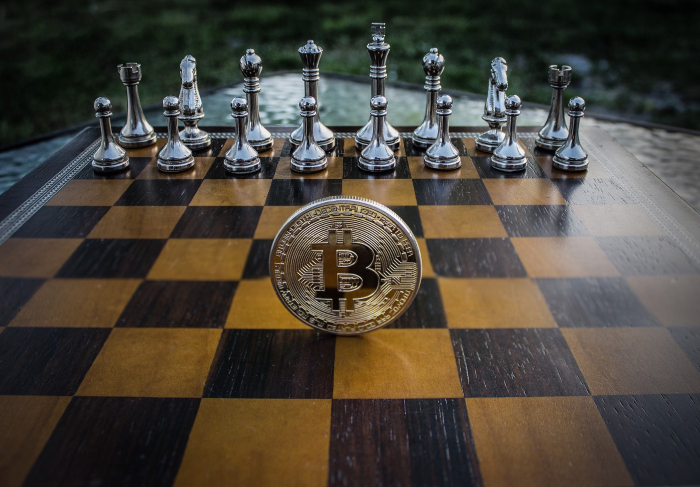 A metal coin with the Bitcoin logo standing on its edge in the middle of a chess board