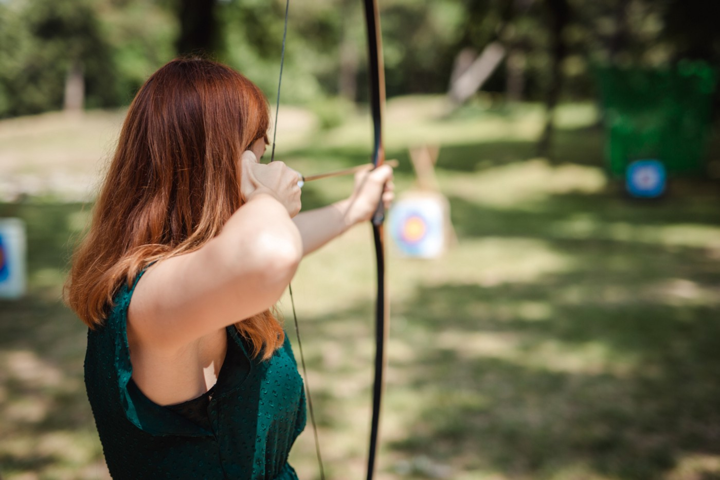 Woman aiming with a bow and arrow at a target.