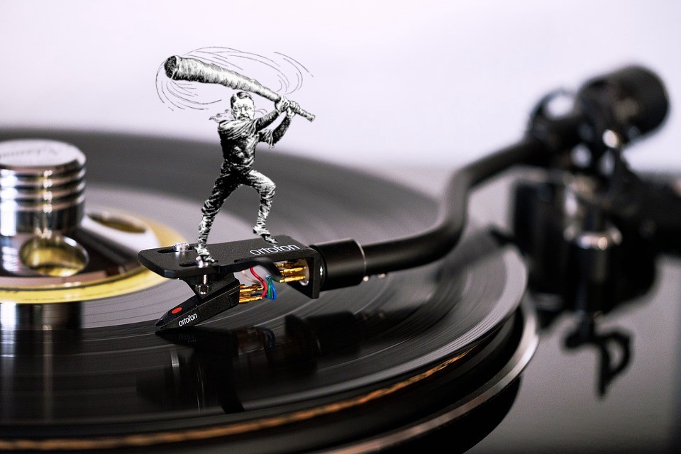 A turntable with a caricature of Teddy Roosevelt as a trustbuster, standing on the tonearm, wielding his 'big stick.'
