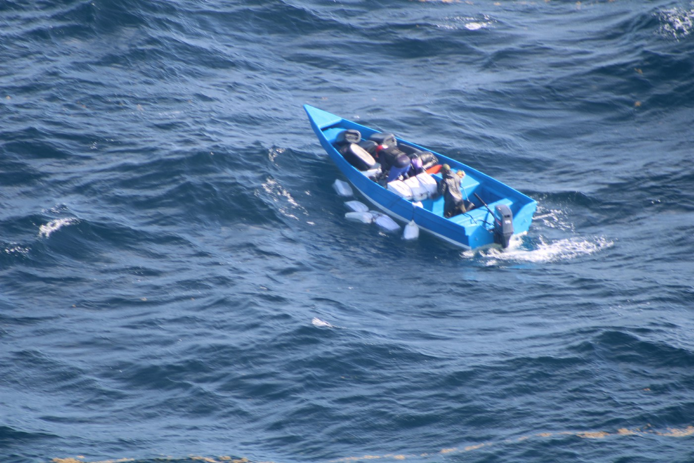 The suspicious small craft with three people on board throwing the large objects overboard.
