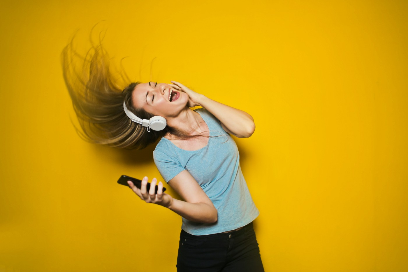 Woman with headphones on dancing to the music with her hair flying up in the air