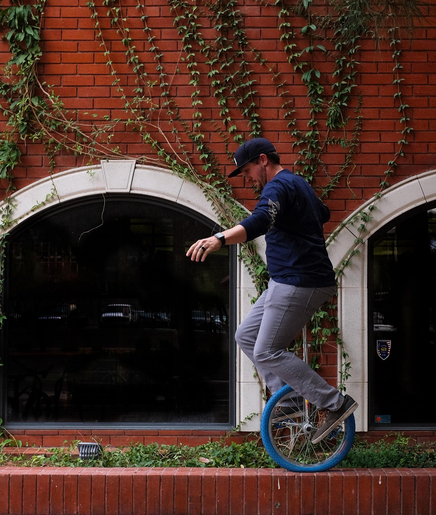 A man rides a blue unicycle atop a low brick wall