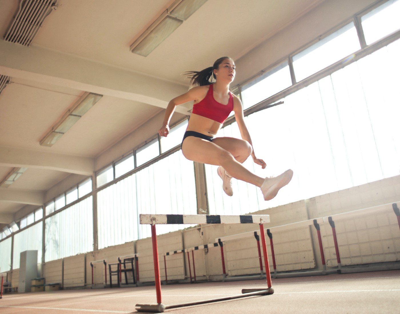 Female athlete jumping over a hurdle in what appears to be a practice jump in an indoor gym.