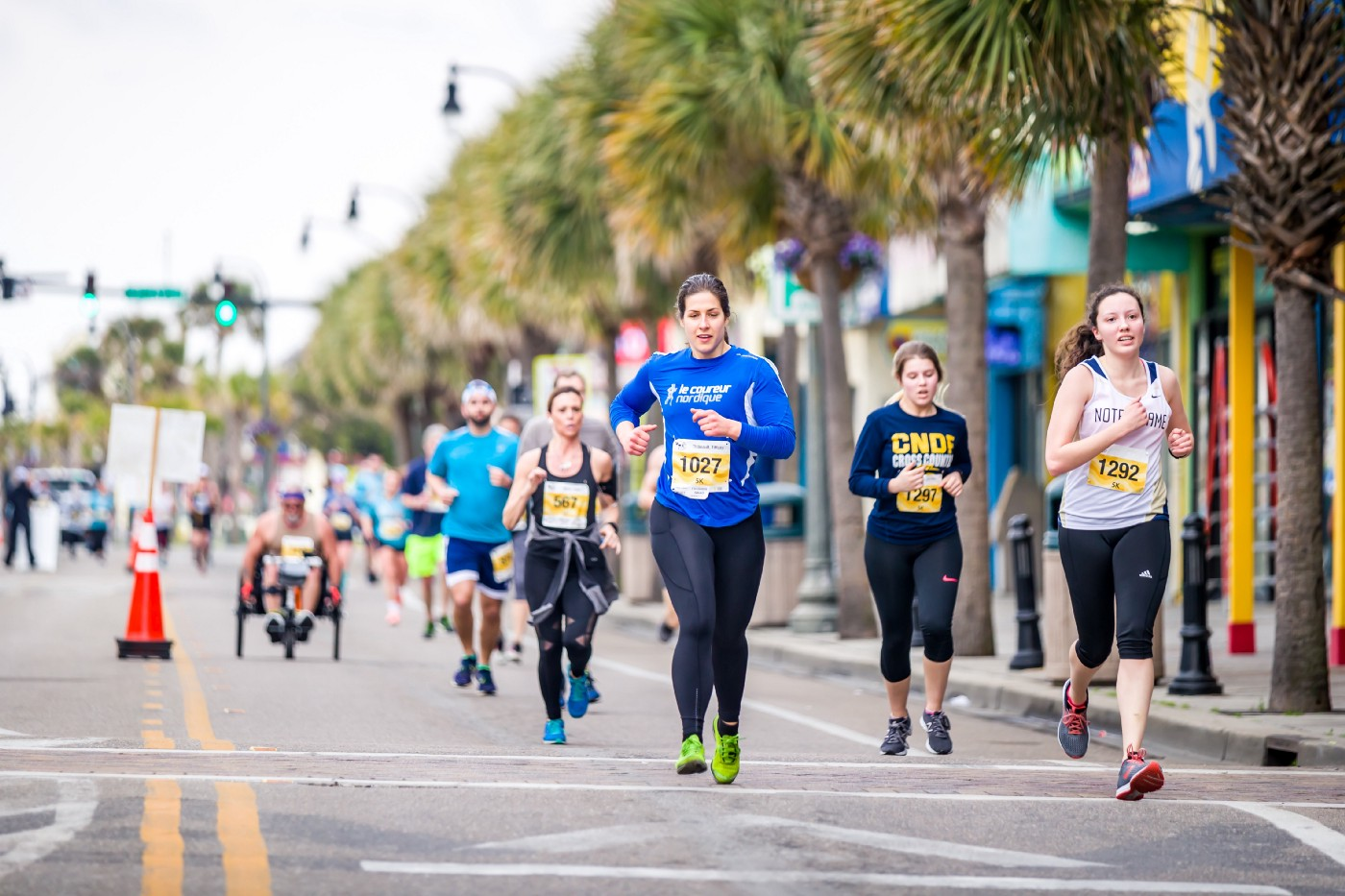 Runners in a marathon. There is also a man in a wheel chair far behind the team of runners. They are running on a city street. Palm trees line the street.