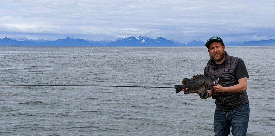 man holding a black rockfish by the ocean