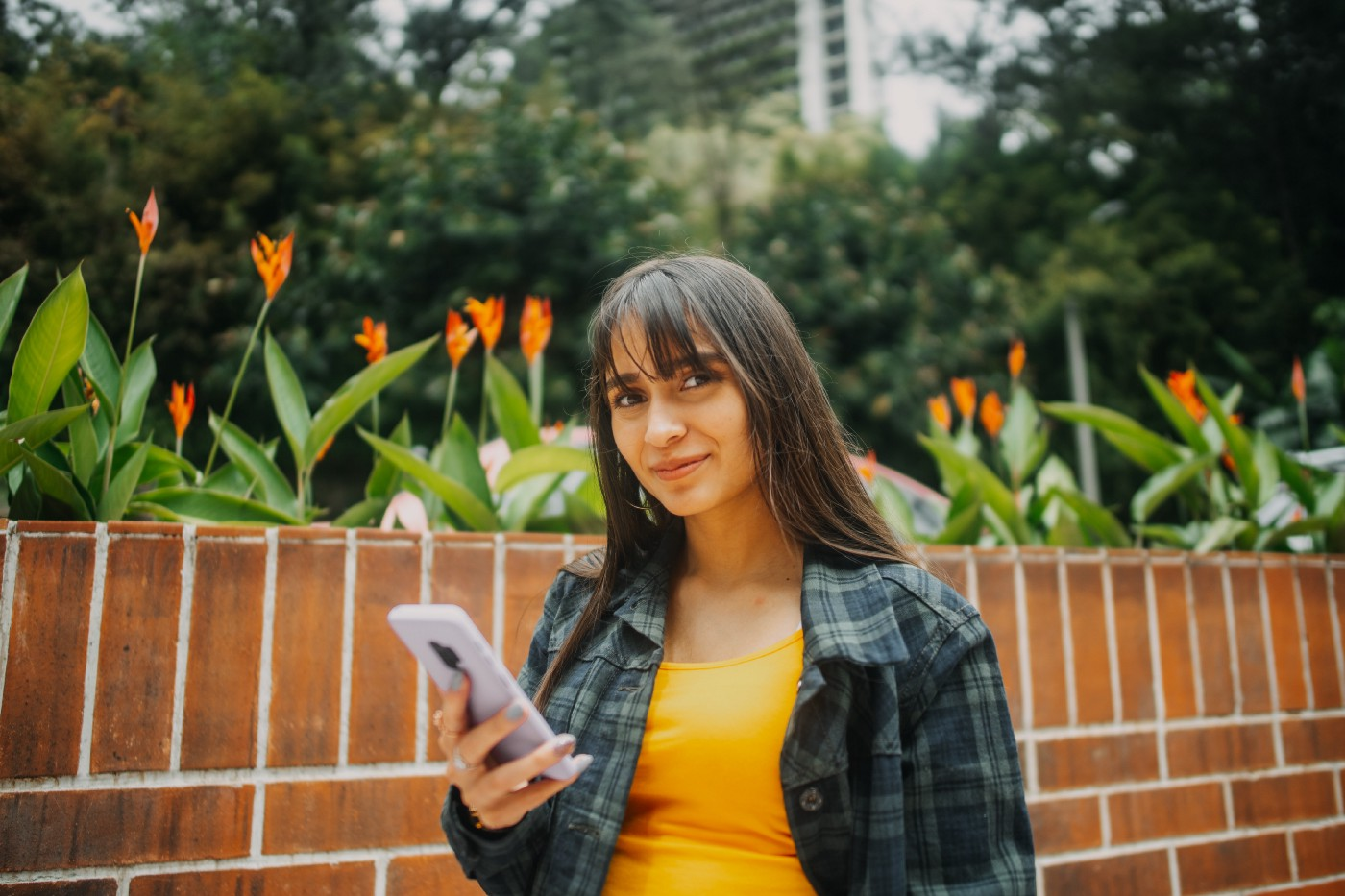 A woman stands in front of a brick wall. She holds an iPhone in her right hand.