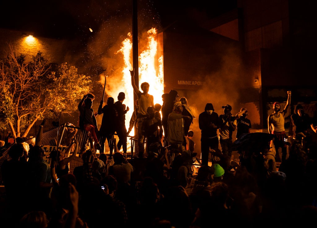 Protestors stand before a burning Third Police Precinct building in Minneapolis after the death of George Floyd.