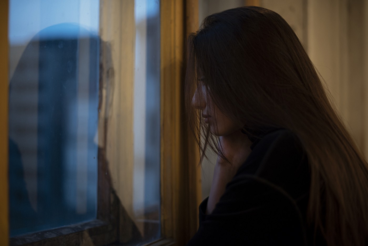 A photo of a sad woman with long hair looking out the window.
