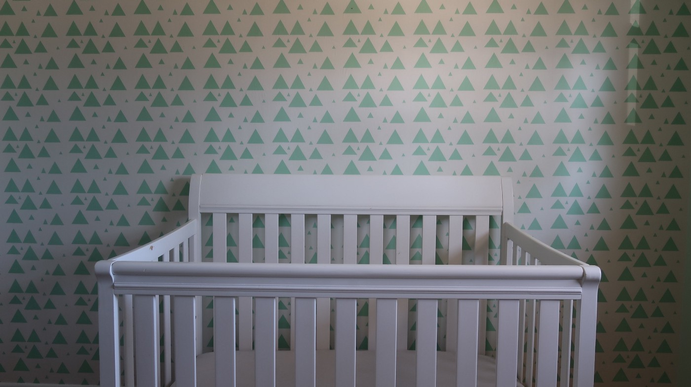 empty crib with green triangle wallpaper