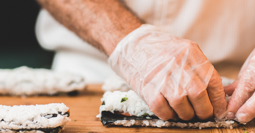 chefs hands wearing vinyl disposable gloves rolling sushi