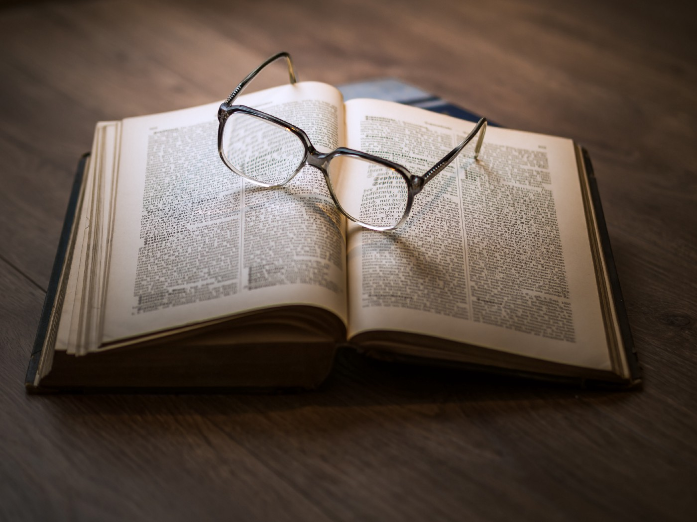 A book is opened to a random page, with a pair of glasses on top of it.