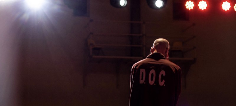 """A photo of the back of a man wearing a collared long sleeve shirt that says """"D.O.C."""""""