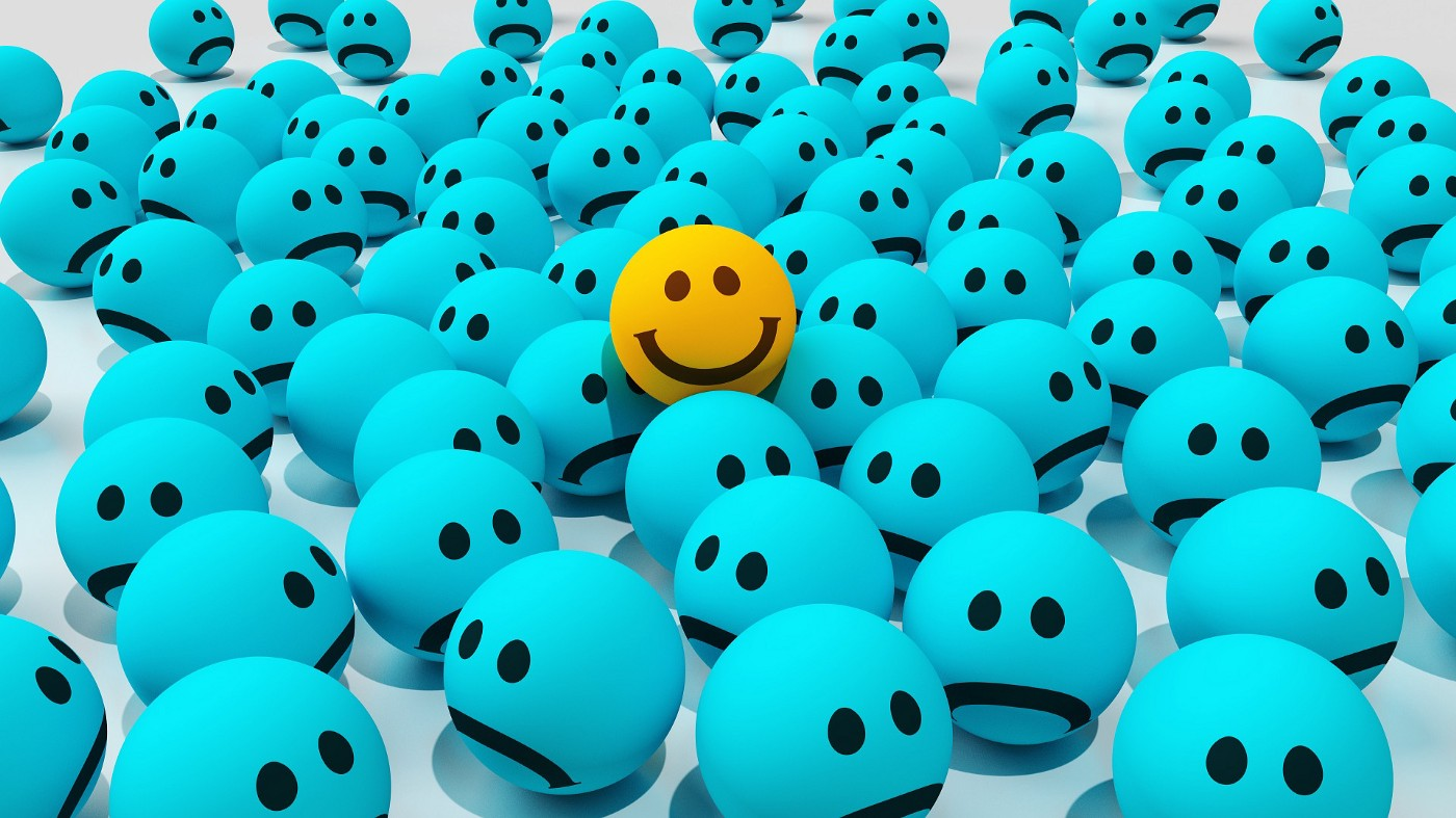 There are blue-colored emojis and they are all frowning. In the middle of the blue emojis is a yellow happy-faced emoji. The happy emoji is surrounded by depressed blue emojis.