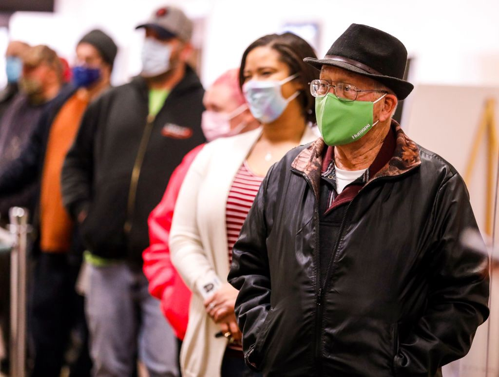 Voters wearing face masks in line at the polls.