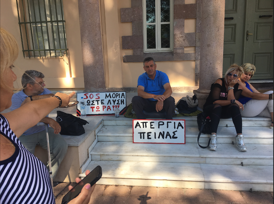 """Anna Koukoulis points to Nick Trakellis and his other supporters on their """"hunger strike"""" outside of the Aegean Ministry."""