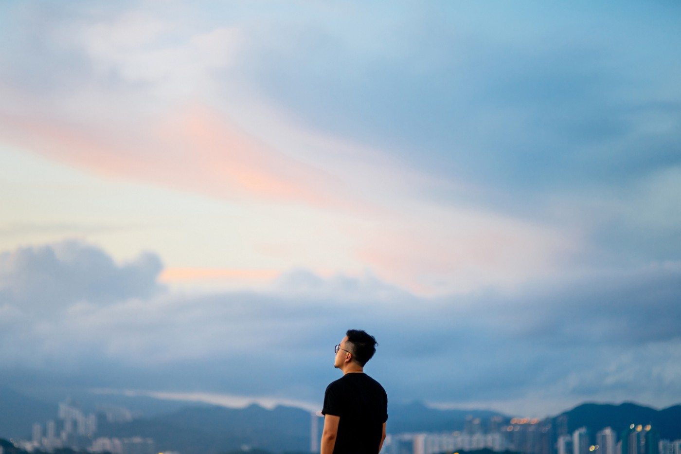 A man looks out at the sky and cityscape.