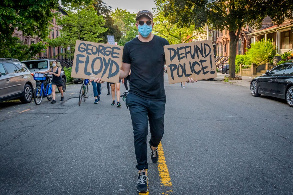 """A photo of a protestor holding up two signs that say """"GEORGE FLOYD"""" and """"DEFUND POLICE!"""""""